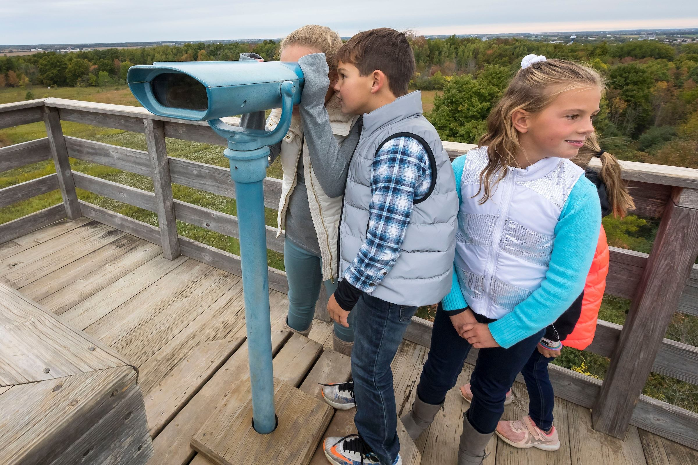 4 kids on top of a tower, 2 are looking through a viewing scope