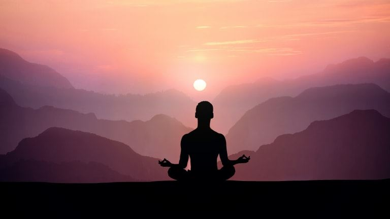 A person doing a sitting yoga pose on a hill at sunset